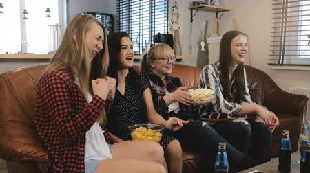 serial : Female friends watch comedy film at home on TV. Happy girls laugh watching funny action movie together 4K slow motion. Stock Footage