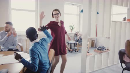 поощрение : Happy European female leader doing dance of victory and success, gives high-fives to multi-ethnic colleagues, laughs 4K. Стоковые видеозаписи