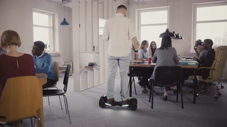 segway : Young male boss using hoverboard to come and talk to colleagues. Confident leader uses technology in modern office 4K. Stock Footage