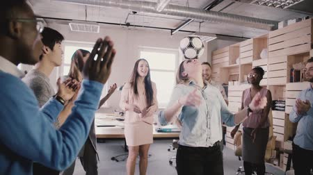 girl claps : European girl juggling football on head in modern trendy office. Multiracial colleagues celebrate clapping, slow motion