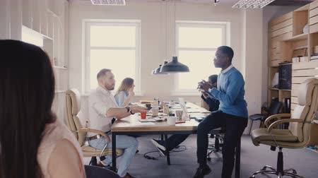 backwards : Camera moves backwards in trendy modern office. Happy multiethnic business people collaborate in loft coworking 4K.