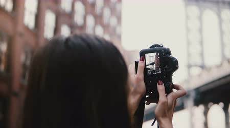 ele geçirmek : Back view happy female tourist with camera takes photos of Brooklyn Bridge from Dumbo viewpoint, New York, walks away 4K Stok Video
