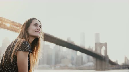 Бруклин : Happy smiling European young woman smiling, enjoying amazing sunset view of New York near Brooklyn Bridge river 4K.