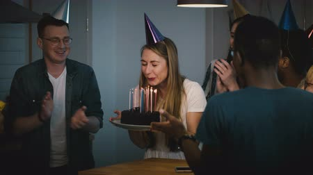 make friends : Attractive girl blows on birthday cake candles. Making a wish. Diverse multi ethnic group celebrate together. Festive 4K
