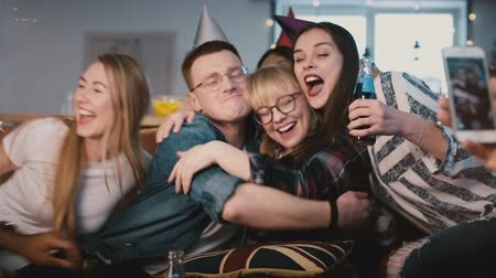 ticker : European woman hugs friends on her birthday party. Happy multi ethnic youth share birthday celebration together. 4K. Stock Footage