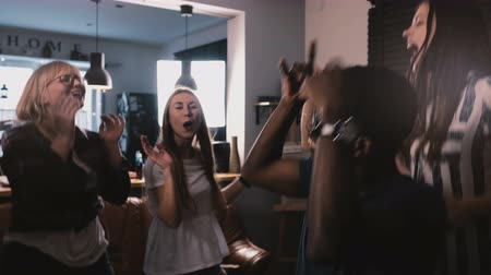 vadon : Successful African American freelance worker celebrating victory with multiethnic colleagues at house party slow motion.