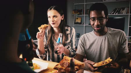 snack : Mixed ethnicity group of happy young friends eating pizza and having drinks at a casual house party by kitchen bar table