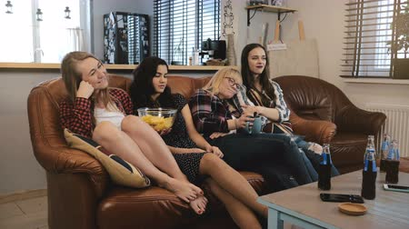 serial : Female friends sit on couch, watch soap opera on TV. Young beautiful girls enjoying romantic comedy slow motion 4K. Stock Footage