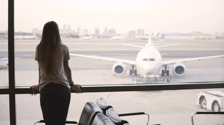 lounge : Young European businesswoman stands looking from airport terminal lounge window, looks at and uses smart watch.