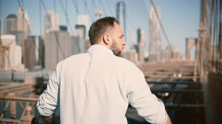 wschód słońca : Back view of adult Caucasian man standing by Brooklyn Bridge rails, enjoying amazing cityscape view and walking away 4K.