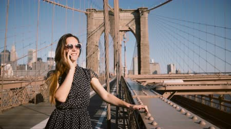 Бруклин : Happy European businesswoman in retro sunglasses talks on the phone, wind blowing in long hair at Brooklyn Bridge 4K. Стоковые видеозаписи