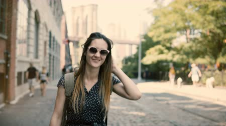 raising hands : Camera follows happy excited European tourist girl with backpack and camera in sunglasses smiling, turning around 4K.