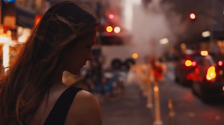ночная жизнь : Close-up view of young beautiful woman standing in New York, America downtown near the traffic road close to smoke pipe.