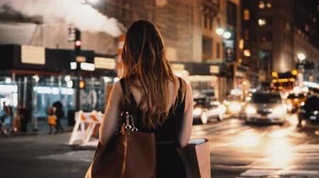cultura juvenil : Young beautiful woman with shopping bags standing near the traffic road in New York, America and using the smartphone. Stock Footage