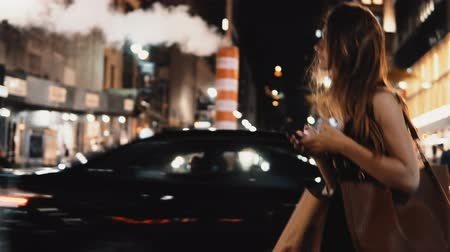 midtown : Young beautiful woman crossing the traffic road in downtown of New York, America in the evening and using smartphone. Stock Footage