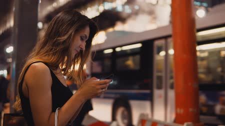 internet things : Young happy woman with shopping bags standing near smoke pipe in traffic downtown of New York and using smartphone. Stock Footage