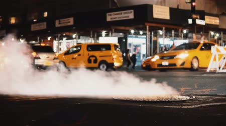 taxi : Close-up view of smoke coming from manhole cover on the traffic road in downtown of New York, America. Stock Footage