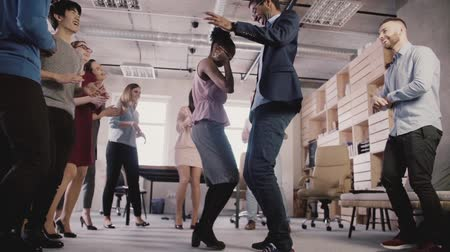 mestiça : Two African American business people doing a fun dance together at casual fun office celebration party slow motion. Stock Footage