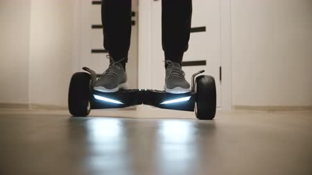 segway : Close-up low angle shot of male legs stepping on gyro scooter in apartment with white walls, moving around and then away