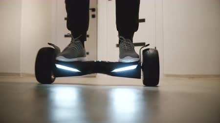 segway : Close-up shot of male legs in sneakers moving around on electric hover board in modern light office with white walls.