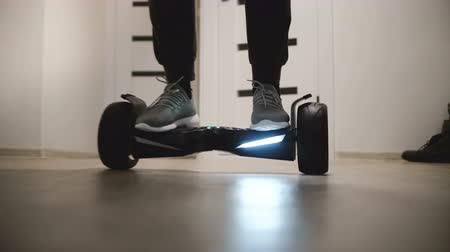 self driving : Close-up view of male legs stepping on electric hyroscooter in modern office space with white walls and moving away. Stock Footage