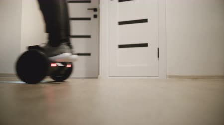 gyro : Close-up view of male legs moving around on electric gyro scooter in apartment with white walls, then walking away.