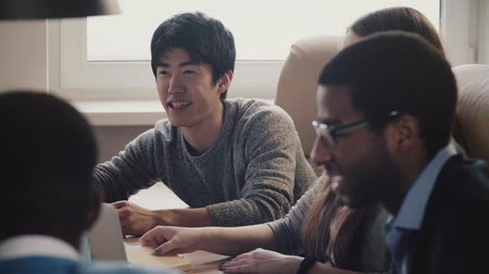 азиатский : Happy confident Japanese young freelance businessman sharing ideas, smiling at multiethnic office meeting slow motion.