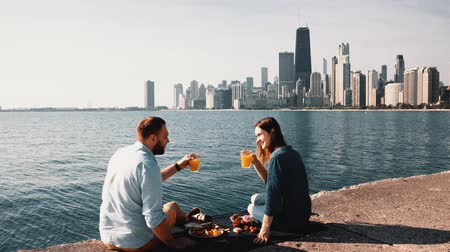 megalopolis : Romantic date on the shore of Michigan lake in Chicago, America. Beautiful couple enjoying a picnic together.