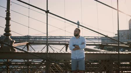 bilezik : Adult Caucasian man standing at Brooklyn Bridge waiting for someone with arms folded, looking at smart watch bracelet 4K
