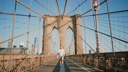 perfect weather : Positive male European tourist walking towards camera, smiling and looking around along Brooklyn Bridge, New York 4K.
