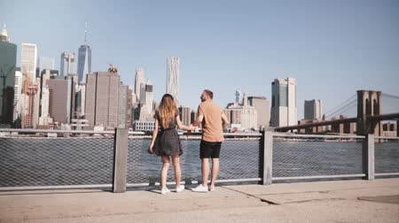 raised : Happy Caucasian couple stand hugging, arms raised at amazing Manhattan skyline in New York, walk unimpressed slow motion