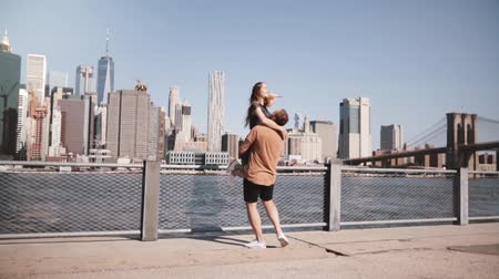 eufória : Happy Caucasian man holding his girlfriend in arms smiling at famous Brooklyn Bridge view in New York slow motion. Stock mozgókép