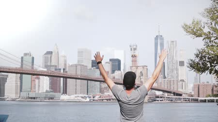 Бруклин : Happy male tourist comes up to famous New York skyline at Brooklyn Bridge river bank fence, feeling joyful and ecstatic