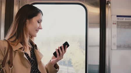 subway car : Businesswoman with smartphone in subway car. Pretty young female commuter using messenger app online. Wireless 5G. 4K Stock Footage