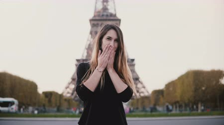 eiffel : Young happy woman standing near the Eiffel tower in Paris, France, smiling at camera and sending the blow kiss. Stock Footage