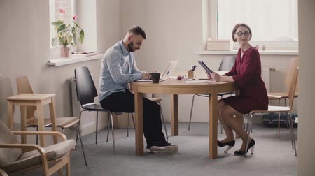 directional : Young female boss sits by the table across male employee with laptop, shows him info on tablet in modern light office. Stock Footage