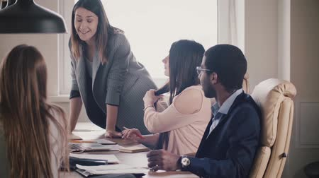 directional : Successful attractive businesswoman encourages multiethnic team. Young female boss leading office meeting by the table. Stock Footage