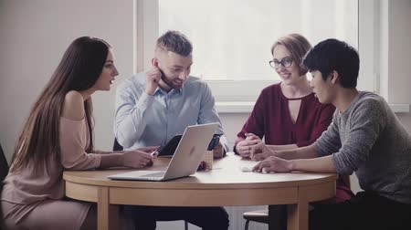 directional : Happy multiethnic young group of business people sit together by the table, discuss international partnership and smile. Stock Footage