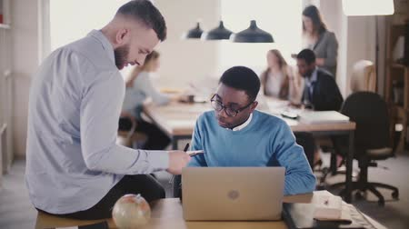 diverso : Multiethnic colleagues collaborate in modern trendy office space, look at a document together, coworking in background. Stock Footage