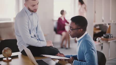 directional : Confident young male CEO businessman is sitting on office table, helping his African American colleague in coworking.