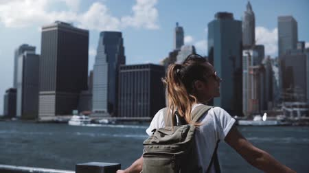 observation deck : Beautiful female traveler with backpack raises arms wide open with excitement near Manhattan city skyline in New York.