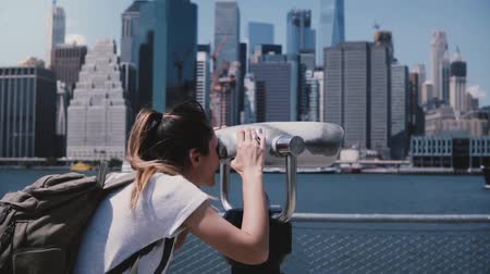 teleskop : Happy female traveler looks through a tower viewer at epic sunny cityscape skyline of Manhattan, New York slow motion. Stok Video