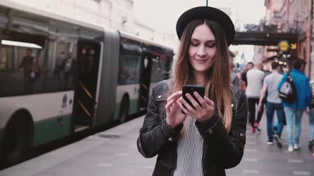 mensageiro : Beautiful young happy European girl in stylish hat walking along busy city street using smartphone app slow motion.