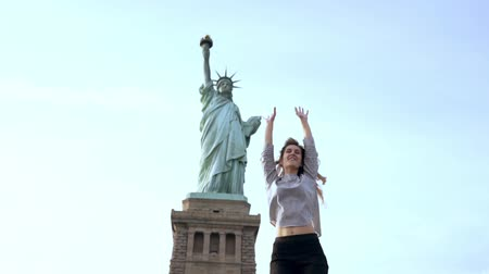 свобода : Successful European female freelance worker jumping high with joy enjoying good living at Statue of Liberty slow motion.
