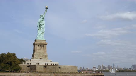 bálvány : Wide panoramic shot of world famous Statue of Liberty national monument and New York City skyline, view from the water. Stock mozgókép