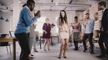 bankier : Happy CEO businesswoman celebrating corporate achievement with a dance at casual multiethnic office party slow motion.