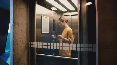 asansör : Young confident woman enters elevator, pushes button, door closes and she rides down using smartphone mobile office app.
