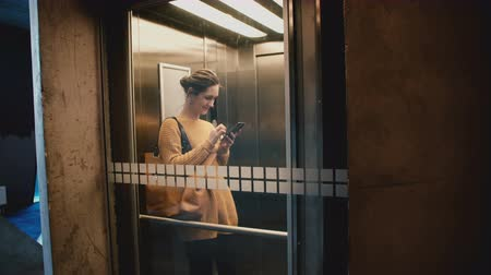 winda : Young happy smiling woman riding elevator with transparent glass wall, walking out using smartphone shopping app online.