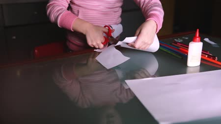 notas : Close-up shot of cute preschool girl in pink sweater cutting shapes with scissors from paper, reflecting in glass table.