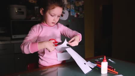 notas : Beautiful little female preschool European child in pink sweater sitting by the table at home cutting paper shapes. Stock Footage